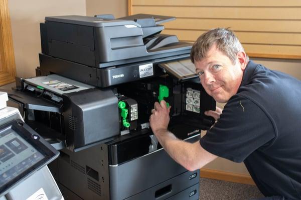 A copier repair technician servicing a Toshiba copier.