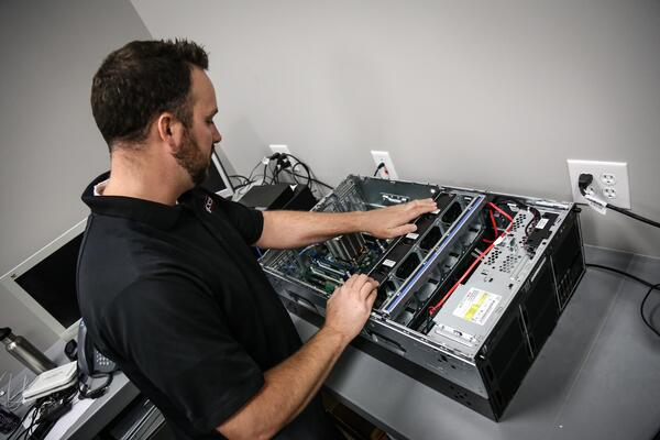 A managed services technician setting up IT hardware.
