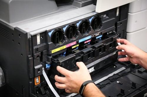 Man replacing toner cartridge